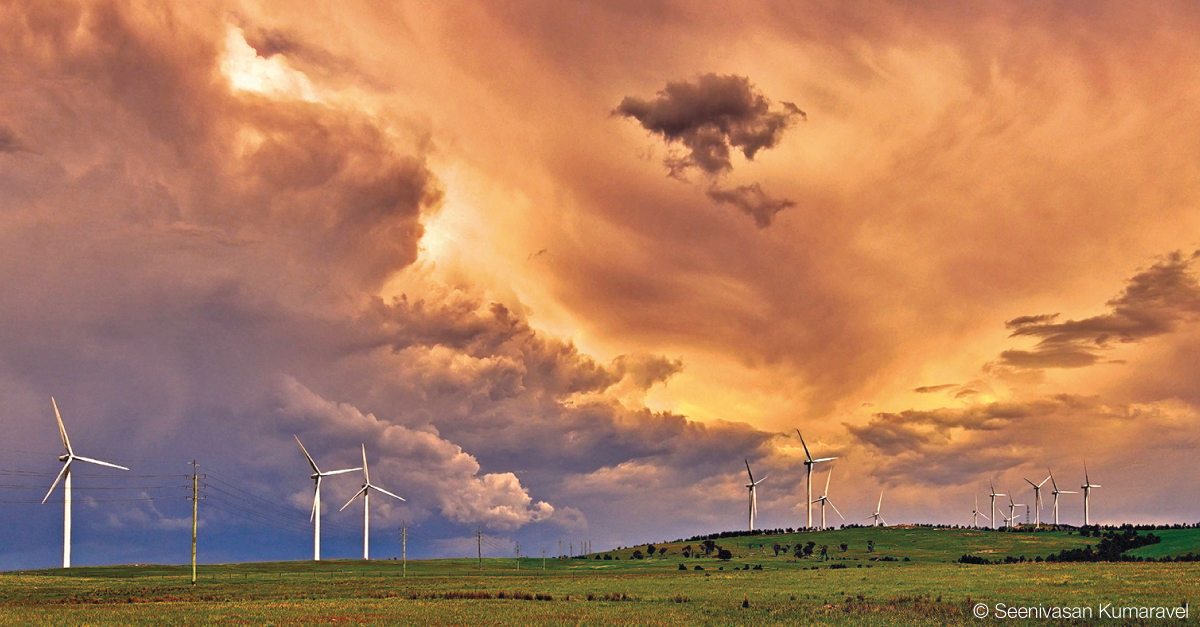 Varied smooth and rough grey clouds over wind turbines on a green hillside.