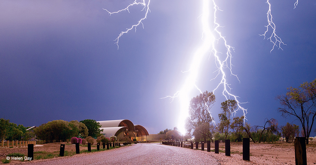 Bright lightning strike with finer 'branches' of lightning extending from the sides, over a road and building.