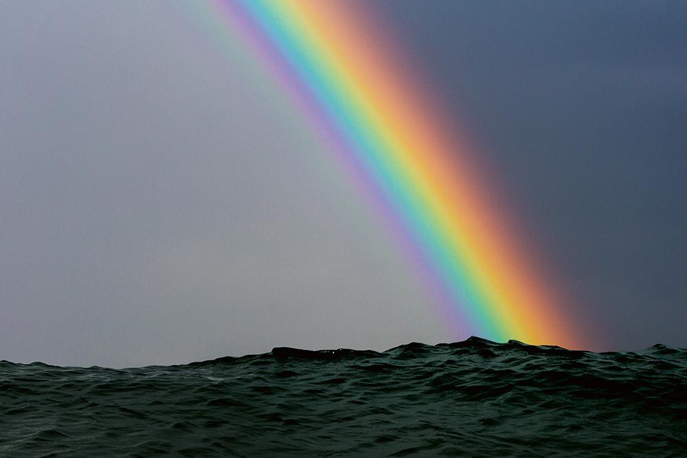 Vivid rainbow in a dark sky resting on top of slate-coloured sea.