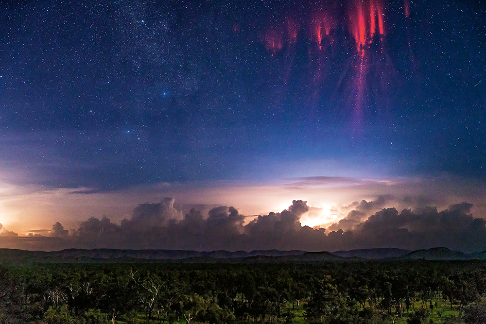Red sprites flicker above a thunderstorm in a starry sky above Kununurra.