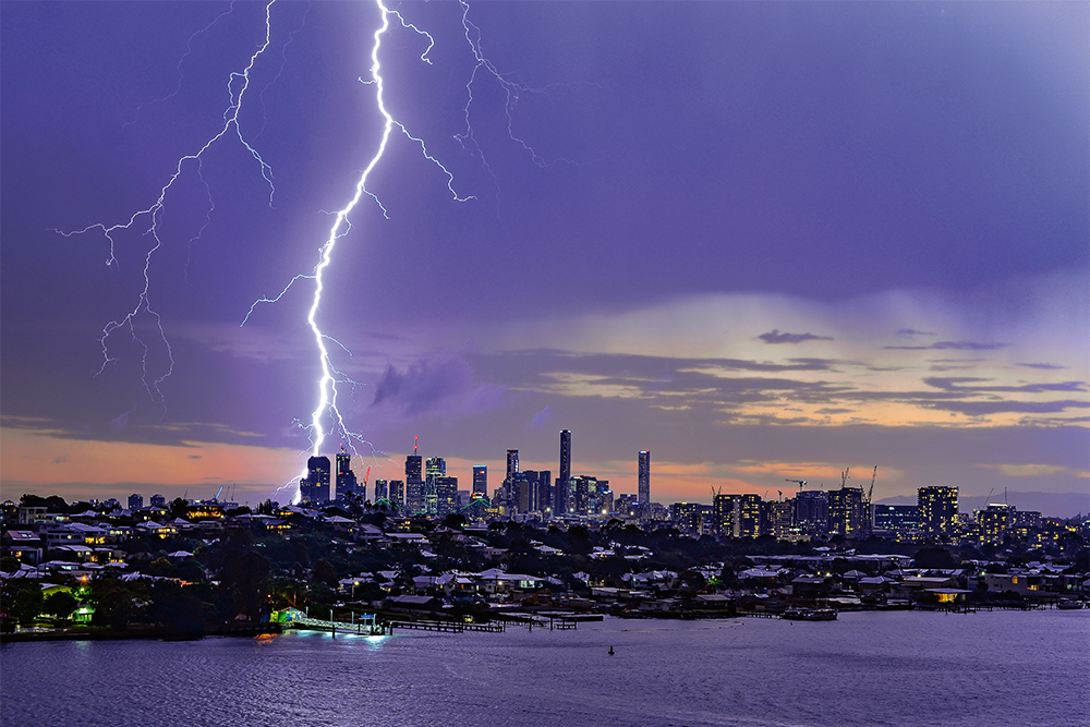 A bright shaft of lightning snakes down a dark sky over the skyline of Brisbane CBD. Secondary bolts (less bright) are to the right and left of the major one.