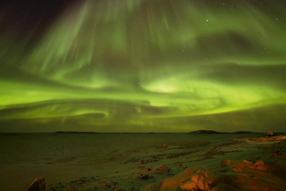 An eerie, green-glowing aurora australis over dark water.