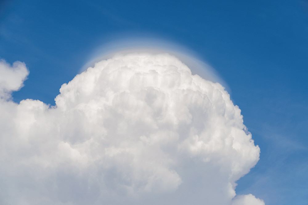 Billowing white cumulus cloud in blud sky with a 'cap' of wispy cloud at the top.