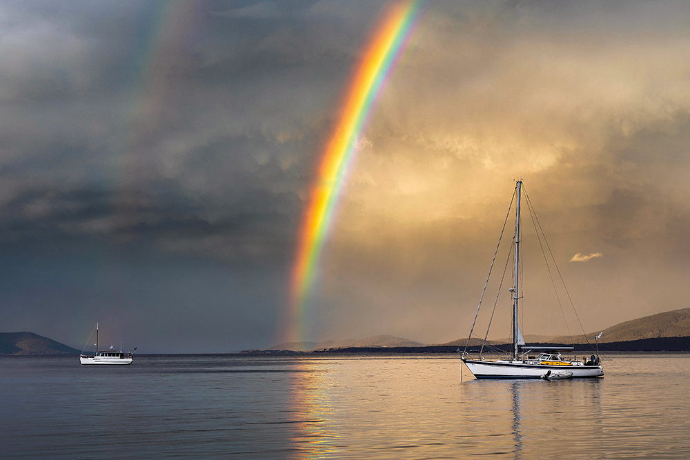 Double rainbow in grey cloudy sky over single-masted boat in the sea. The brighter rainbow is reflecting in the water.
