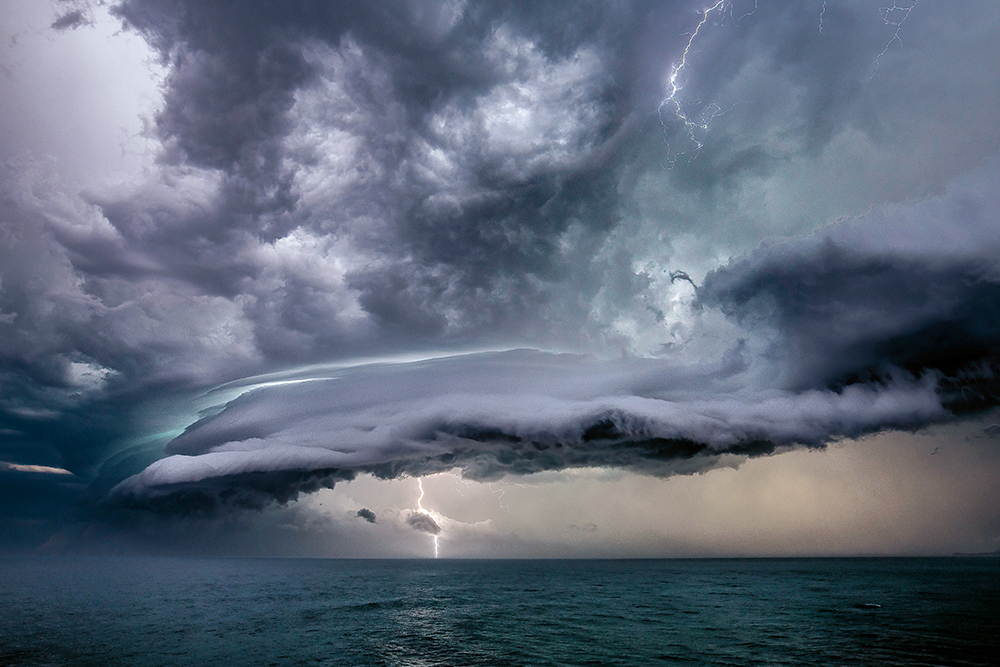 Shelf cloud in stormy sky with lightning striking down to the grey sea.