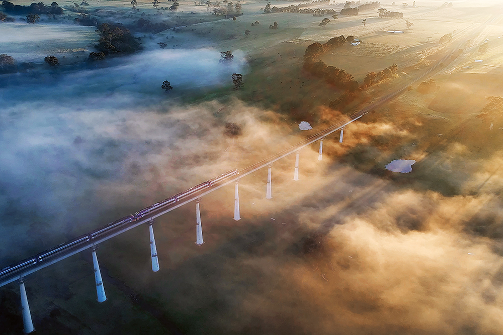 An aerial image of a fog-filled valley, with the sun casting long rays through it and a train crossing a bridge.