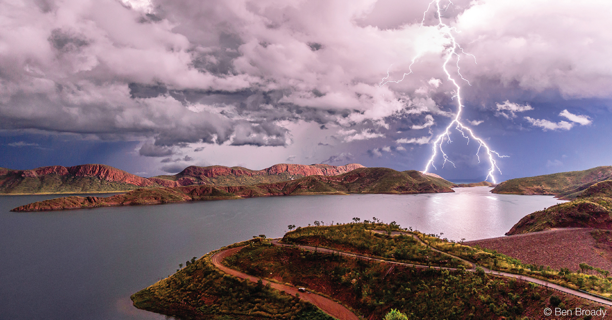 Lightning strike from a cloudy sky over a lake
