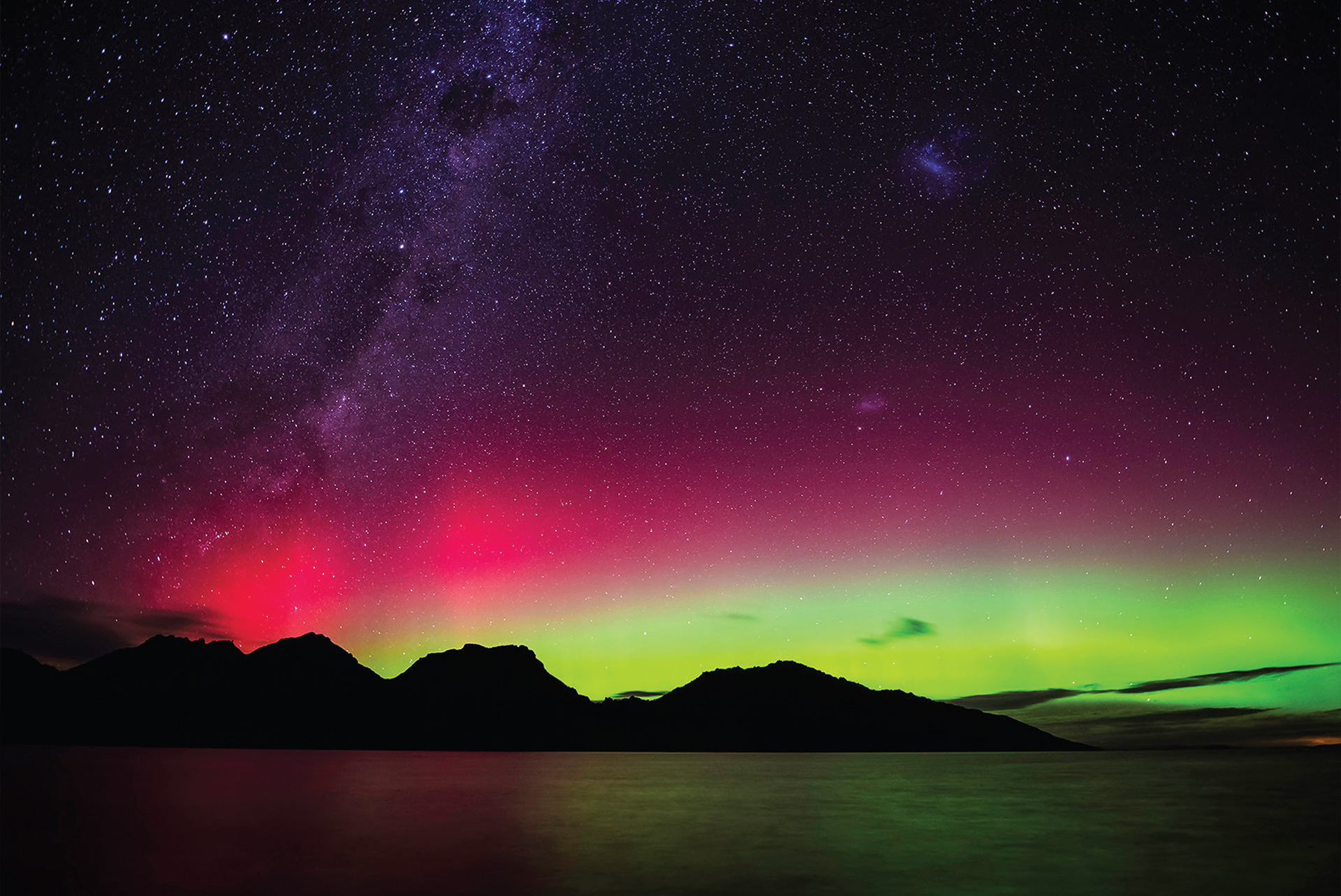 Purple, pink and green layers of light in the night sky, over silhouetted hills and sea, which reflects the colours