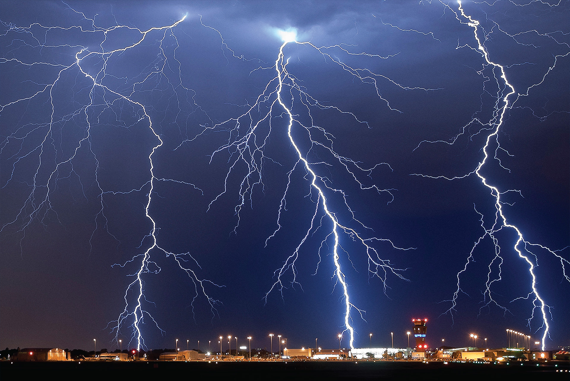 Three branching lightning strikes in a night sky over airport building and control tower