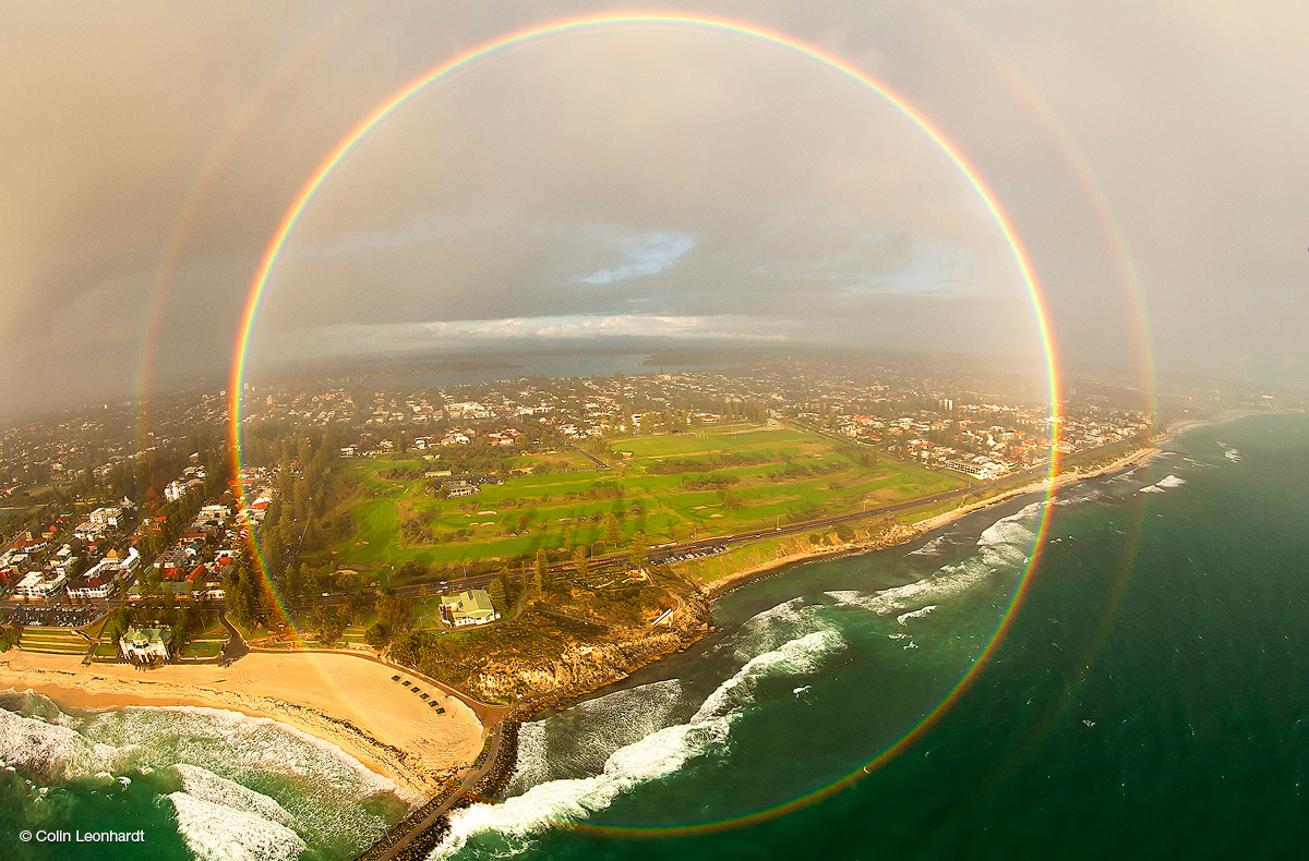 Circular double rainbow above sea, shore, paddocks and houses, with a grey, cloudy sky