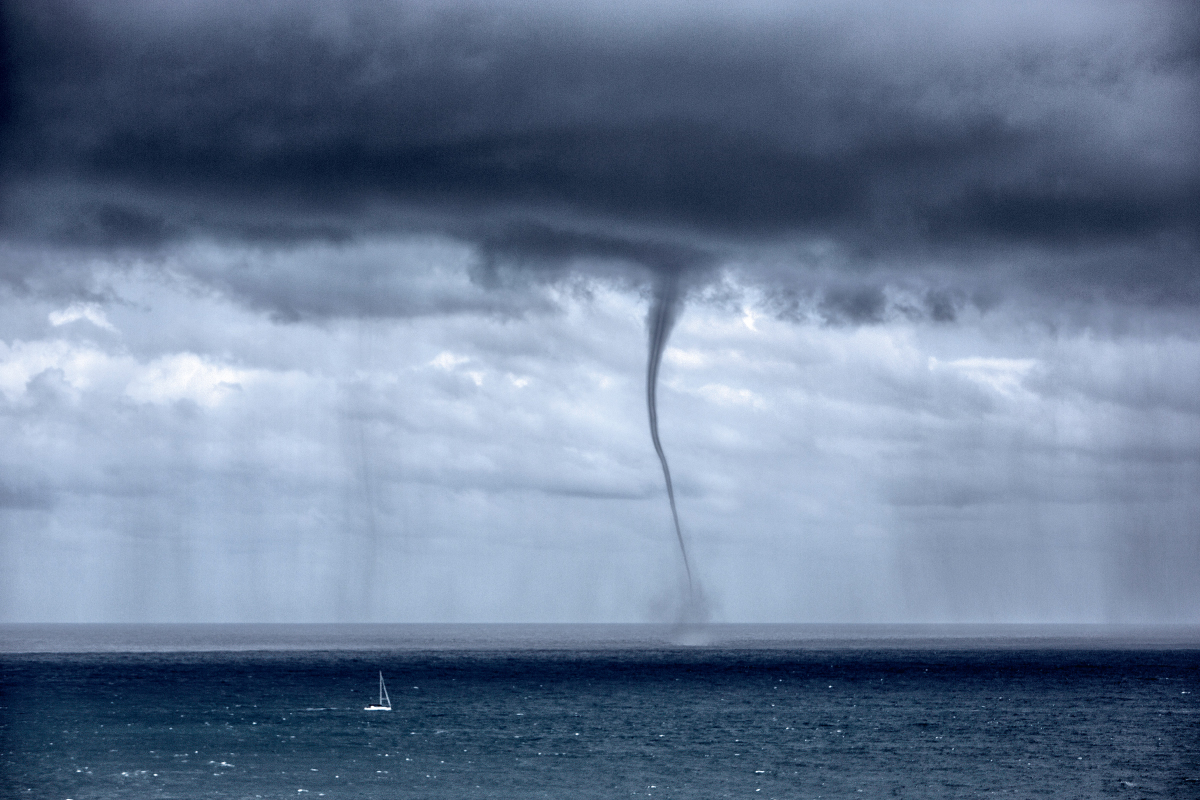 Waterspout dropping from grey clouds over the ocean, amid heavy rain.