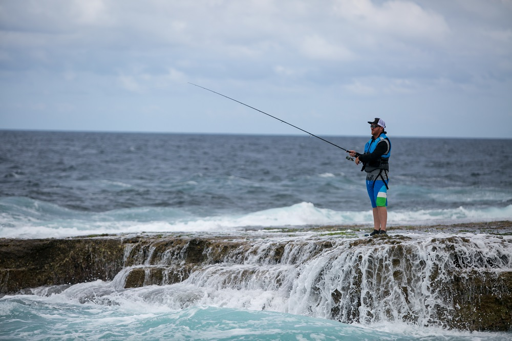 A man wearing a life jacket stands fishing on a rock shelf with shallow water running back into the ocean.