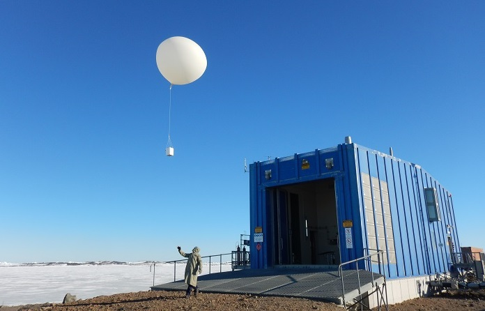 Person launching large white weather balloon at Davis Station