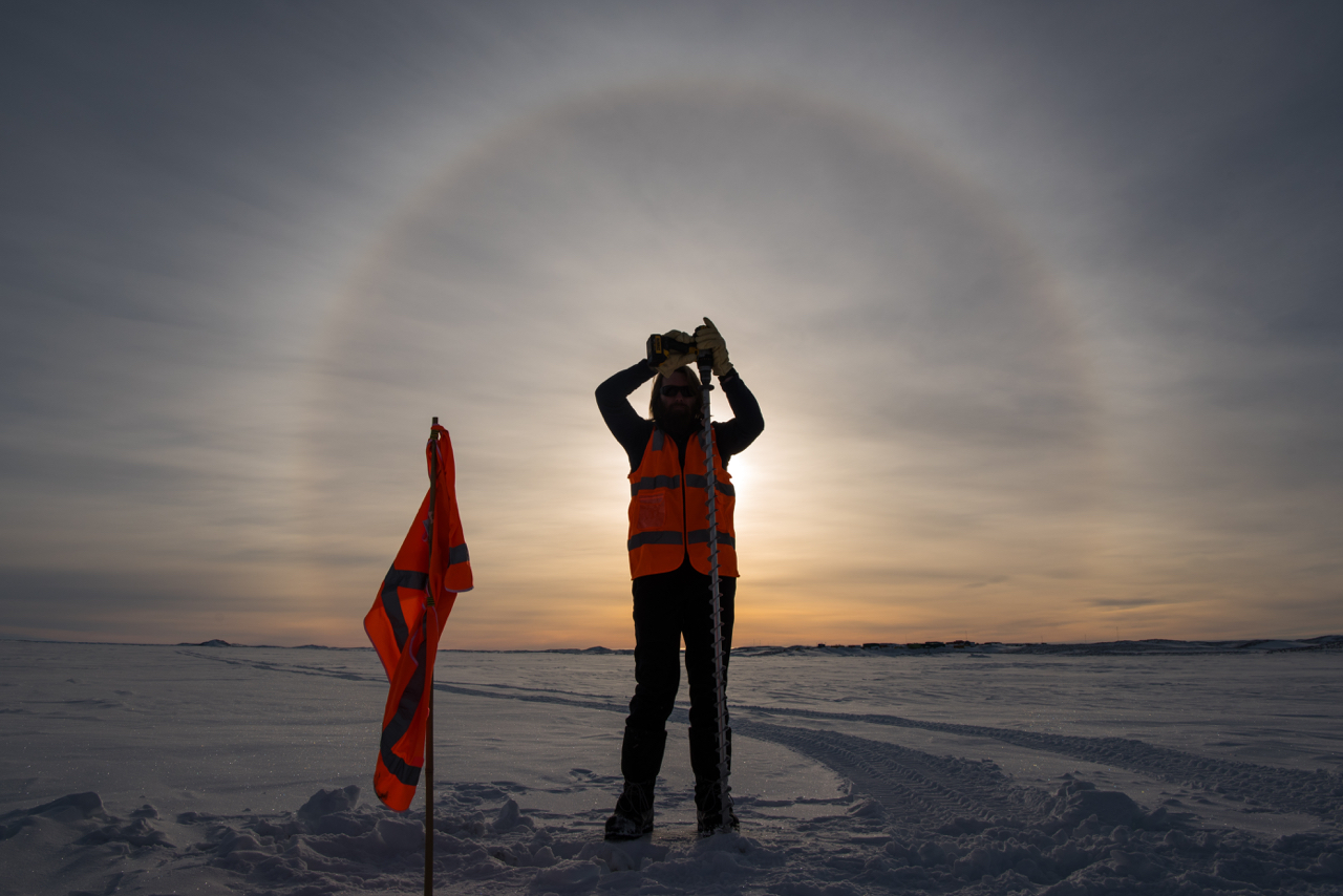 Image: An AAD staff member drills sea ice to measure its thickness, beneath a sun halo. Credit: Barry Becker