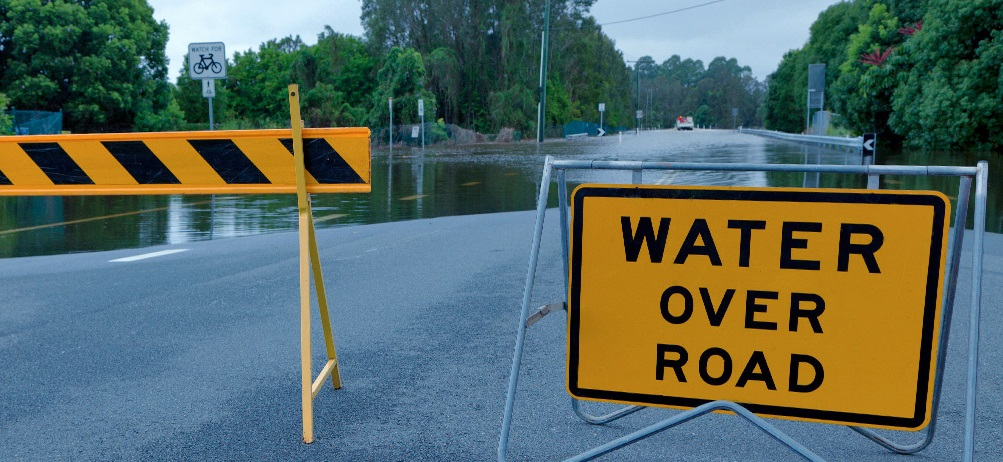 Image: Sign warning of water over road, ahead of section of road underwater. Credit: SES NSW
