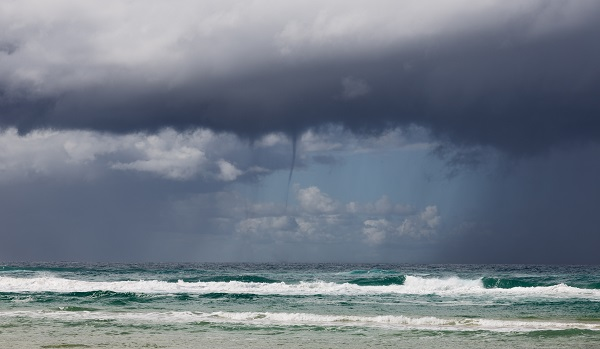 Waterspout emerging from grey clouds above ocean waves.