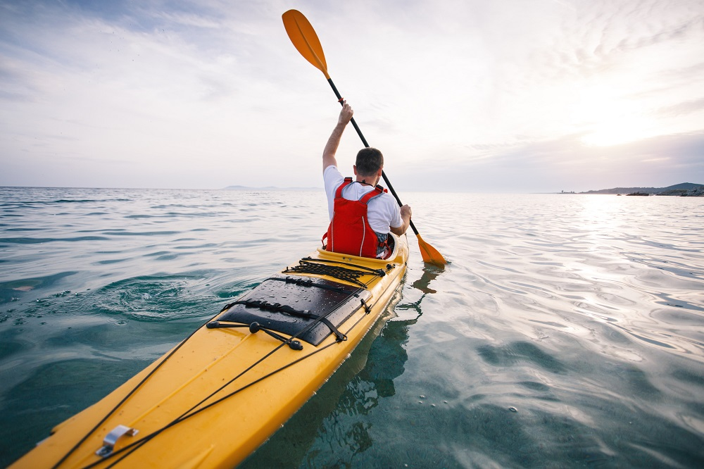 A kayaker in a yellow kayak paddles in the sea.