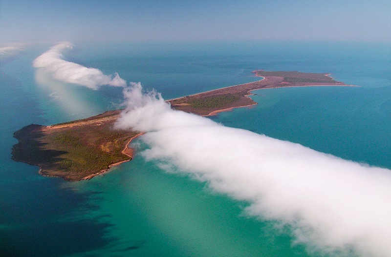 Taken from the air, this image looks down on a long white cloud above Sweers Island, surrounded by turquoise seas.