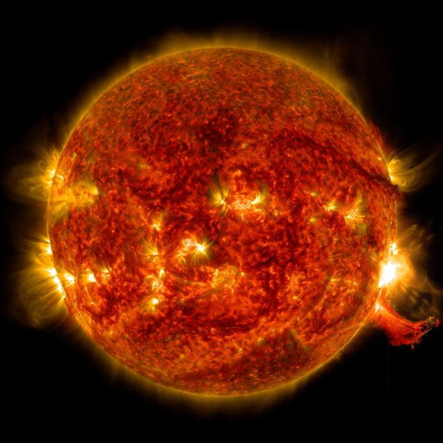 The sun as an orange globe, with patches of yellow light, including a bright solar flare.