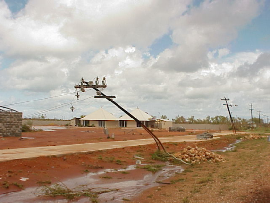 A steel power pole is bent down over the footpath by the force of the wind. The sky is cloudy and the earth red; there's a couple of houses in the background.