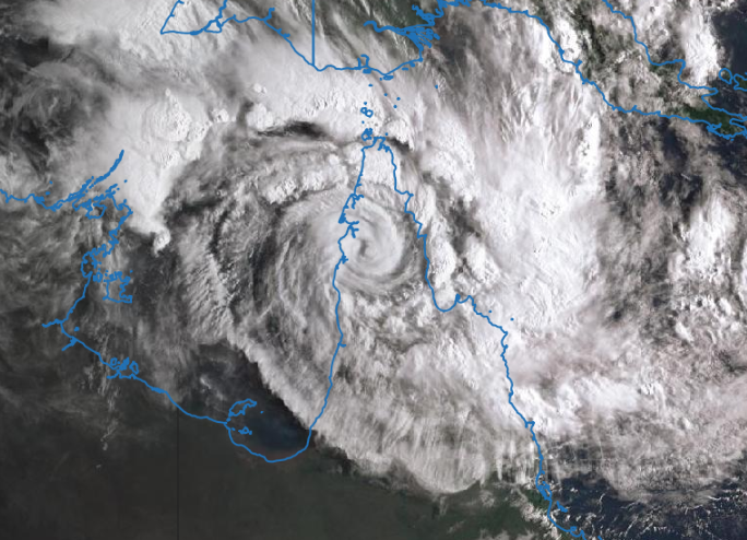 Satellite image with Australia's edge visible as a blue line over the clouds, which display the classic cyclone spiral band patter.