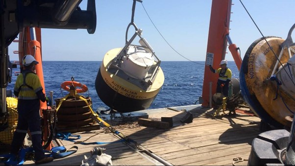 Large Australian tsunami detection buoy being launched into the sea from the deck of a ship.